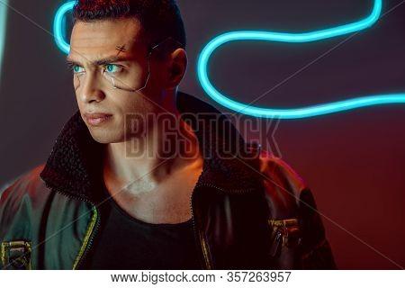 Handsome And Bi-racial Cyberpunk Player Looking Away Near Neon Lighting On Black