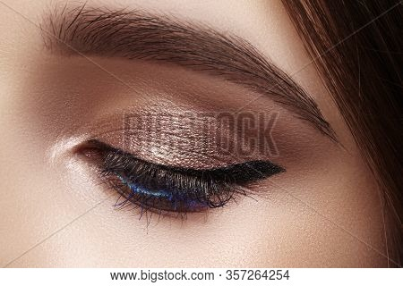 Beautiful Macro Shot Of Female Eye With Classic Eyeliner Makeup. Perfect Shape Of Eyebrows, Brown Ey