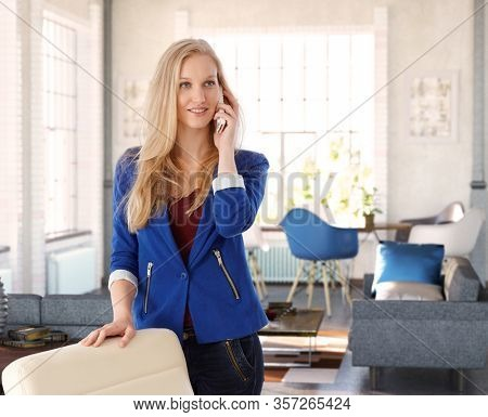 Home office - Young blonde woman talking on mobilephone at home.