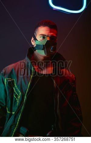 Bi-racial Cyberpunk Player In Protective Mask Near Neon Lighting On Black