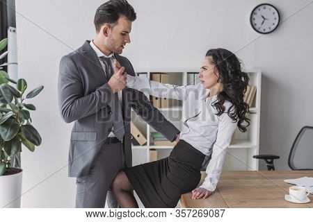 Angry Secretary Sitting On Desk And Pushing Away Businessman Molesting Her In Office