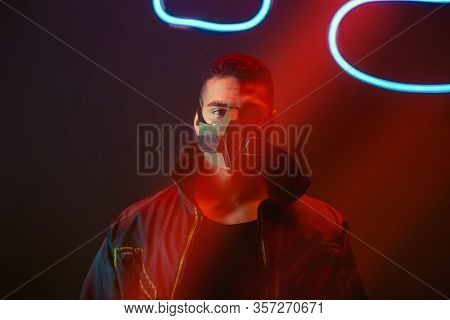 Bi-racial Cyberpunk Player In Protective Mask Looking At Camera Near Neon Lighting On Black
