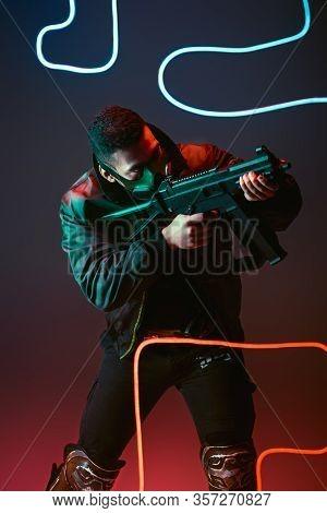 Bi-racial Cyberpunk Man In Protective Mask Aiming Gun Near Neon Lighting On Black