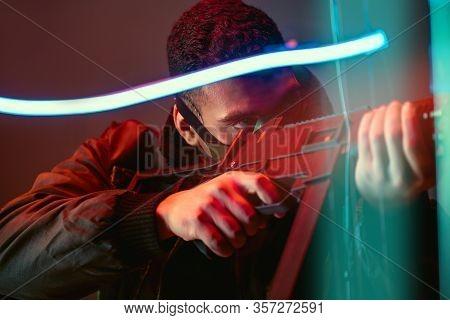 Selective Focus Of Bi-racial Cyberpunk Player In Protective Mask Aiming Gun Near Neon Lighting On Bl