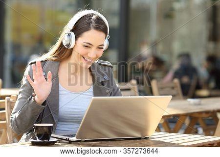 Happy Woman Wearing Wireless Headset Videocalling On Laptop Sitting In A Cafe Terrace