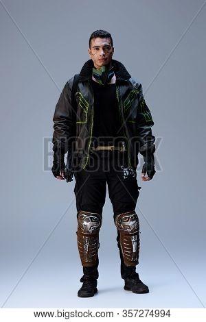 Handsome Bi-racial Cyberpunk Player Standing On Grey