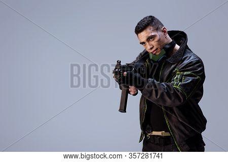 Handsome Bi-racial Cyberpunk Player Holding Gun Isolated On Grey