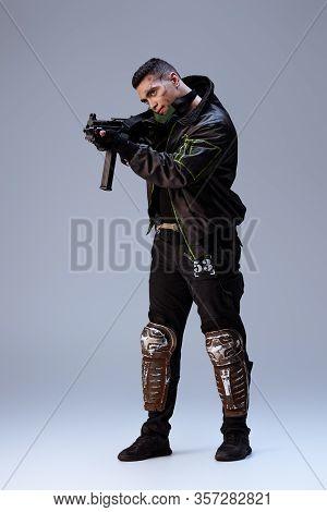 Handsome Bi-racial Cyberpunk Player Aiming Gun On Grey