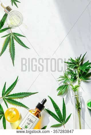 Various Glass Bottles With Cbd Oil, Thc Tincture And Marijuana Leaves On A Marble Background. Flat L
