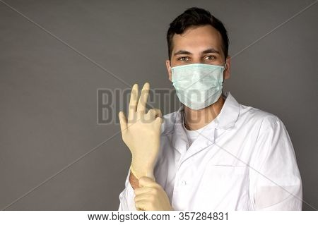 Portrait Of A Doctor In A Medical Gown Putting On Gloves Before Conducting Tests For Coronavirus. Ph