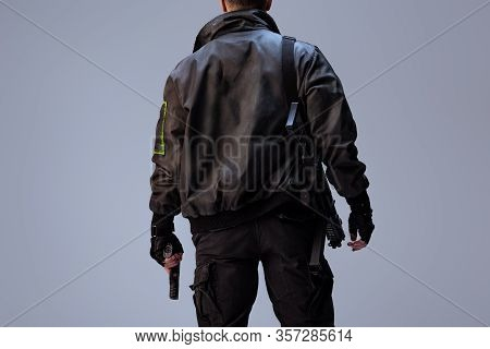 Back View Of Cyberpunk Player Holding Gun While Standing Isolated On Grey