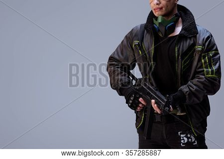 Cropped View Of Armed Bi-racial Cyberpunk Player Holding Gun Isolated On Grey