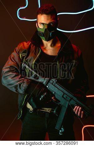 Bi-racial Cyberpunk Player In Protective Mask With Gun Near Neon Lighting On Black
