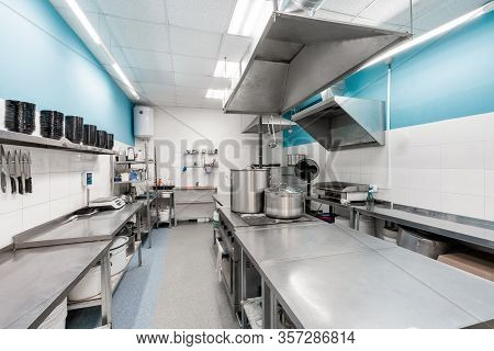 Modern Restaurant Kitchen With Stainless Steel Kitchenware And Equipment. Cooking With Preparation T