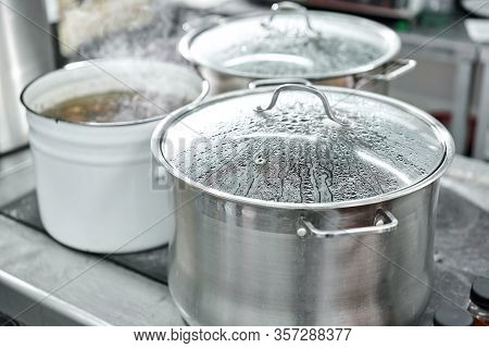 Closeup Of Large Pots On The Stove. Chef Cooking At Commercial Kitchen - Hot Job. Real Dirty Restaur