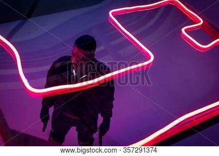 Overhead View Of Armed Bi-racial Cyberpunk Player Holding Guns Near Red Neon Lighting