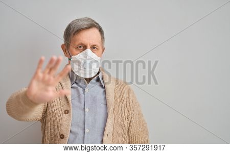 Old man wearing facemask during coronavirus and flu outbreak. Virus and illness protection, home quarantine. COVID-2019