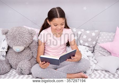 Bedtime Reading Fun. Happy Girl Read Book To Toy Friend. Small Child Enjoy Reading Fiction Story. Re