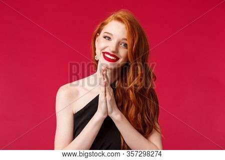 Close-up Portrait Of Hopeful Smiling European Woman With Red Long Curly Hair, Black Dress And Lipsti