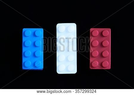 Blue And Red Toys With A White Paracetamol Tablet Representing The French Flag On A Black Background