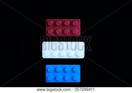 Blue And Red Toys With A White Paracetamol Tablet Representing The Dutch Flag On A Black Background.