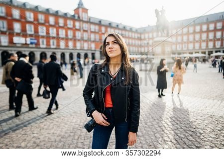 Female Tourist Holding Camera In Front Landmark Plaza Major Square In Madrid,spain.young Woman Photo