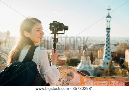 Female Travel Photographer/cinematographer And Bloger Using Camera With Gimbal Stabiliser Crane In B
