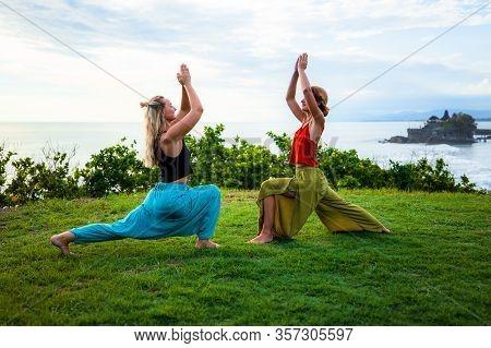 Couple Yoga. Two Young Women Practice Virabhadrasana I, Warrior I Pose And Ashwa Sanchalanasana, Equ