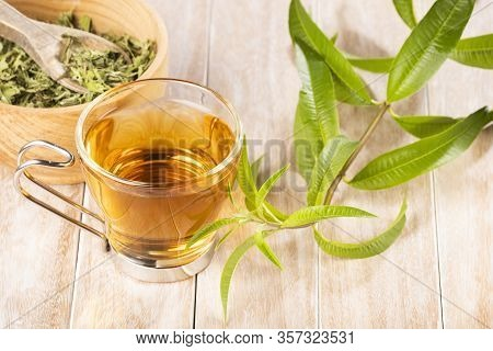 Lemon Verbena Leaves On Wooden Bowl And Verbena Tea On Wooden Table. Aloysia Citrodora