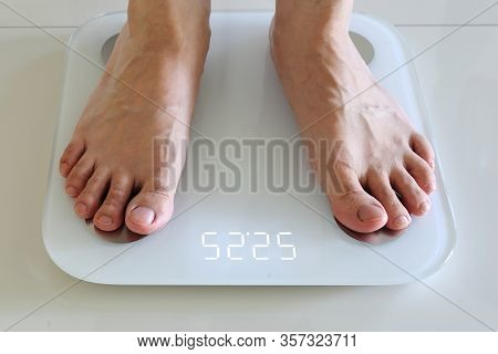 Bare Feet Standing On A Scales. Lose Weight Concept With Person On A Scale Measuring Kilograms. Weig