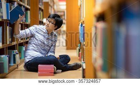Smart Asian Man University Student Wearing Glasses Reading Book By Vintage Bookshelf. Textbook Resou