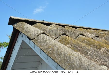 Asbestos Rooftop Against Blue Sky. House Asbestos Rooftop.