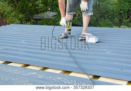 Roofer With Screw Gun Installing  Corotile Lightweight Metal Roofing Sheets Roofing  Construction