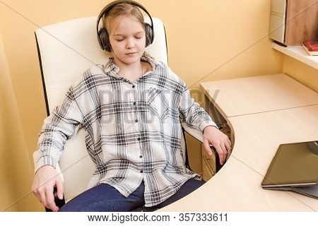 Young Girl With Headphones Or Earphones Listening To Music Or Chatting On Home Tablet. Runaway Into
