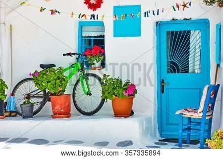 Street with whitewashed house and bicycle near wall in Mykonos island, Greece