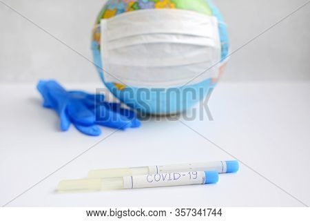 Coronavirus 2019. Pandemic. Mask Mode. Masked Globe, Perks And Laboratory Analysis On A White Backgr