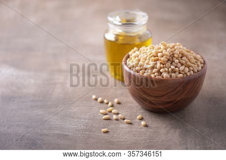 Shelled Raw Pine Nuts In Wooden Bowl And Pine Nuts Oil In Bottle On Wood Textured Background. Copy S