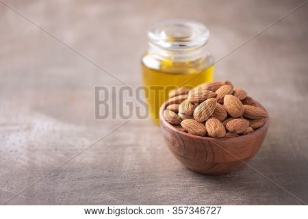 Almond Nuts In Wooden Bowl And Almond Oil In Bottle On Wood Textured Background. Copy Space. Superfo
