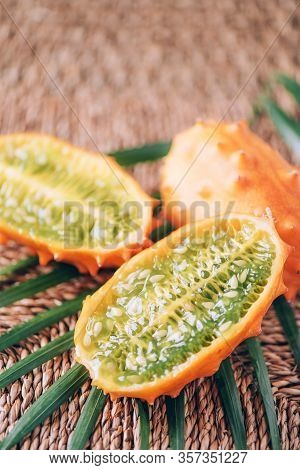 Kiwano Or African Horned Melon With Palm Leaves On Rattan Background. Cutted Hedged Gourd, African H