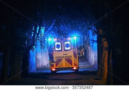 Rear View Of Ambulance Of Emergency Medical Service Against Dark Alley. Themes Rescue, Hope And Heal