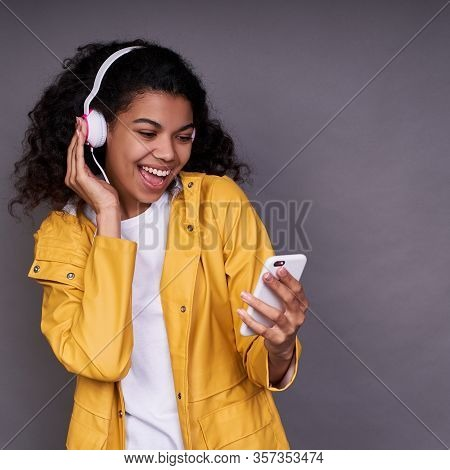 Charming Happy Young African American Girl In White T-shirt And A Yellow Raincoat, With Curly Hair,