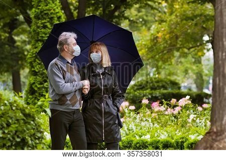 Senior Man And Woman In Face Mask. Virus Outbreak. Retired Couple Walking In A Park Under Quarantine