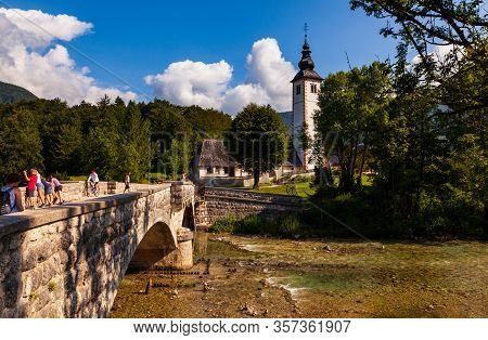 Bohinj, Slovenia - August, 01: View Of Bohinj Lake With St John The Baptist Church And Bridge On Aug