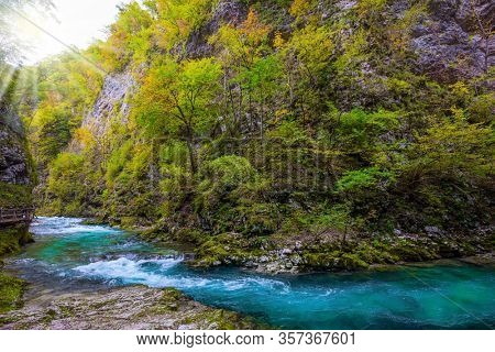 Mountain river with azure water. Bubbling and roaring foamy rapids, rocks and rifts.  Slovenia. Vintgar gorge. The concept of active and photo tourism