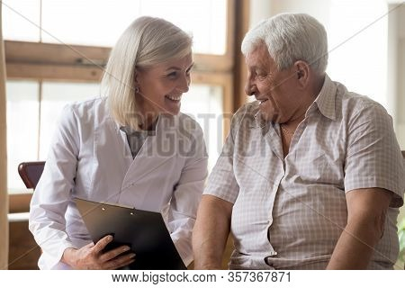 Happy Mature Female Doctor Consulting Patient About Good Checkup Result