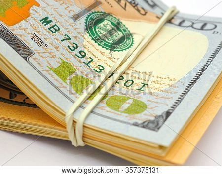 Dollars Lies On A White Paper Background. Above - A Hundred-dollar Bill Of New Sample. Fragment Clos