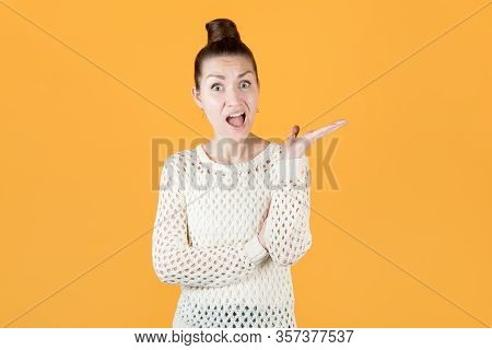The Girl Is Indignant And Questions, Gesturing, Isolated On Orange-yellow