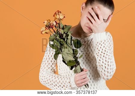 Girl Covers Her Face In Crying, She Holds Withered Flowers In Her Hands. Isolated On Orange-yellow