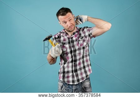 A Hard Worker With A Hammer In His Hand Scratches His Ear With His Finger. He Has A Crippled Shirt A