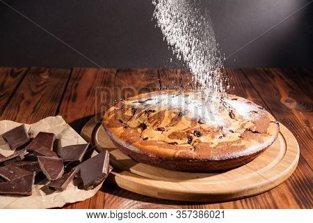 Rustic Chocolate Cake Sprinkled With Icing Sugar. Chocolate Cake On A Wooden Table.